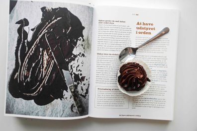 A chocolate cupcake on a cookbook